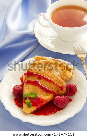 Delicious pancakes with berries  and raspberry sauce.
