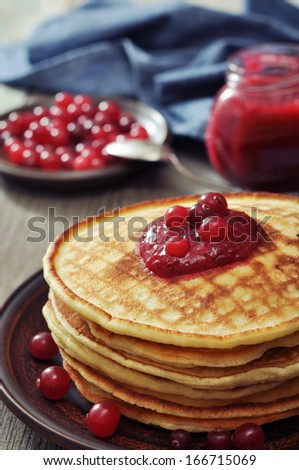 Delicious pancakes with cranberry jam on the wooden background - stock photo