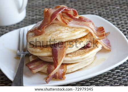 Delicious pancakes with crispy bacon and maple syrup