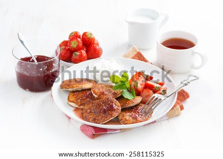 Delicious pancakes with fresh strawberries on a plate, jam and tea, horizontal, close-up - stock photo