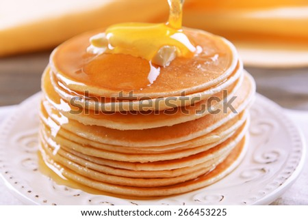 Delicious pancakes with honey on plate on table close-up - stock photo
