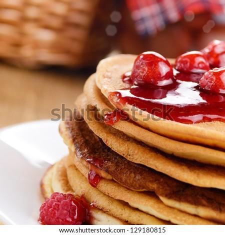 Delicious pancakes with raspberries on the kitchen table - stock photo
