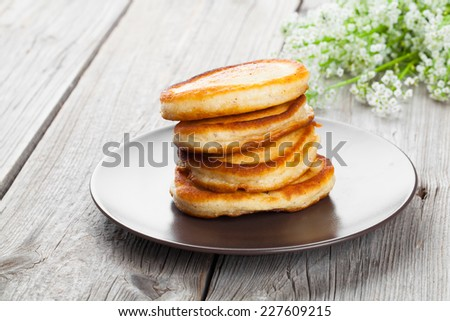 Delicious pancakes with raspberries sauce on the wooden kitchen table - stock photo