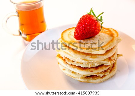delicious pancakes with strawberry and tea