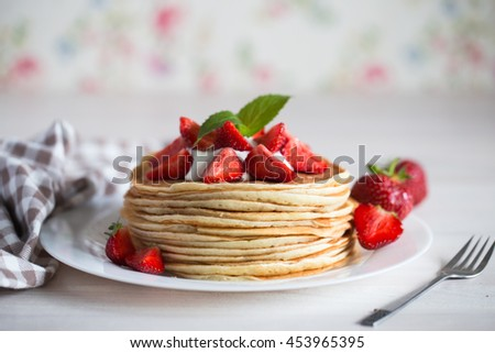 Delicious pancakes with strawberry on wooden background - stock photo