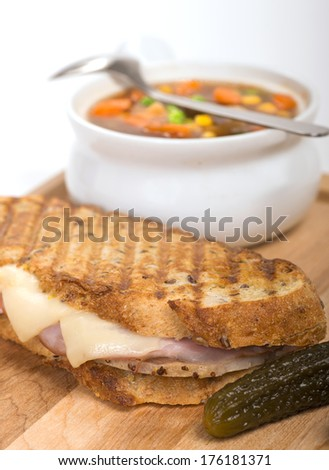 Delicious panini made with ham, pork and swiss cheese served with a vegetable soup, and pickles - stock photo