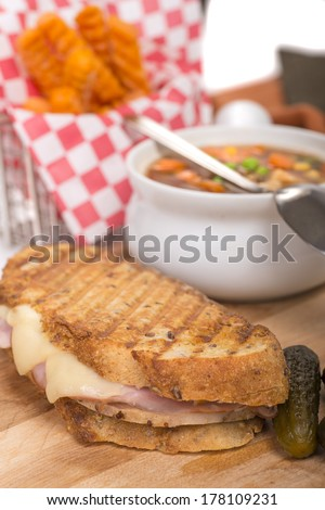Delicious panini made with ham, pork and swiss cheese served with a vegetable soup, pickles and sweet potato french fries - stock photo