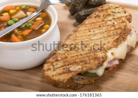 Delicious panini made with ham, pork and swiss cheese served with a vegetable soup, sweet potato fries and pickles - stock photo