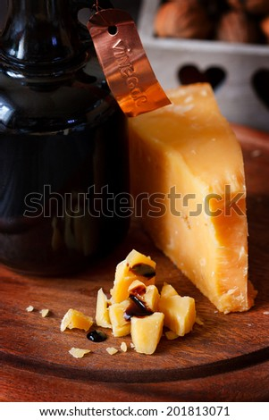 Delicious parmesan cheese and bottle of old balsamic vinegar - stock photo