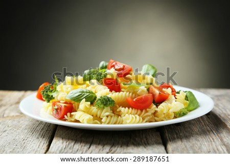 Delicious pasta on plate on grey wooden background - stock photo