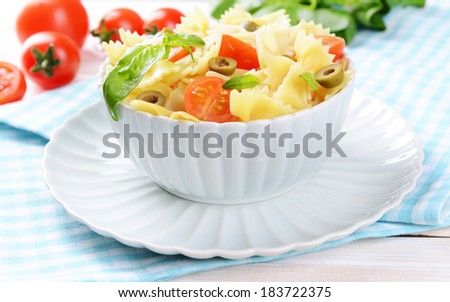 Delicious pasta with tomatoes on plate on table close-up - stock photo