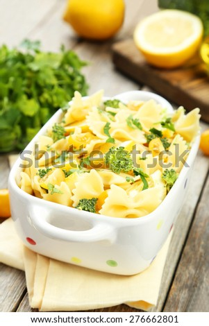 Delicious pasta with with broccoli in bowl on grey wooden background