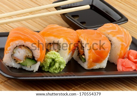 Delicious Philadelphia Sushi with Wasabi, Marinated Ginger and Soy Sauce in Black Square Shape Bowl with Pair of Chopsticks on Straw mat background - stock photo