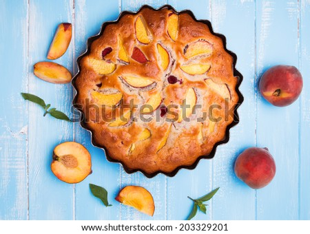 Delicious pie with peaches and raspberry on the blue background, up view - stock photo