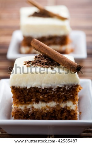 Delicious pieces of carrot cake with cinnamon stick - stock photo