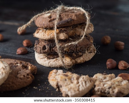 Delicious pile of chocolate chip cookies on dark wooden background - stock photo