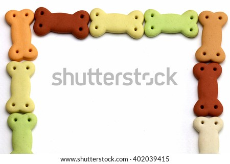 Delicious Pile of dog biscuits in the shape of a bone for pet food, in square frame shape for background use. - stock photo