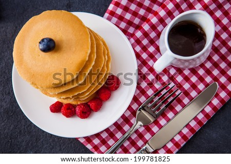 Delicious pile of hot homemade pancakes with fresh raspberries and blueberries and a jug of maple syrup - stock photo