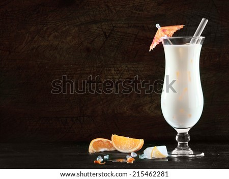 Delicious pina colada cocktail with rum, cream of coconut and pineapple for an exotic beverage to celebrate the Christmas and New Year festive season, on black with copyspace - stock photo