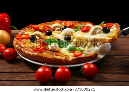 Delicious pizza and fresh vegetables on wooden background, close up - stock photo