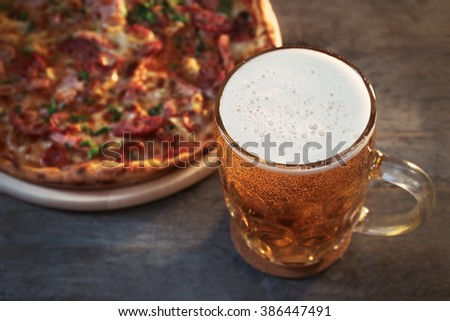 Delicious pizza  and glass of beer are on wooden table - stock photo