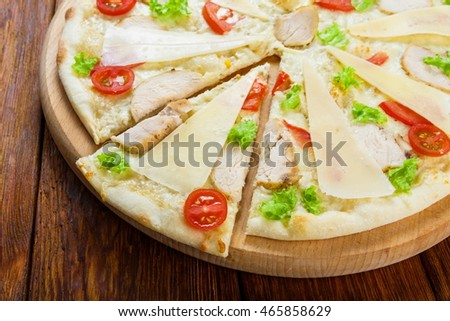 Delicious pizza Caesar style with white sauce, chicken, parmesan, cherry tomatoes and fresh lettuce - thin pastry crust at wooden table background, one piece cut
