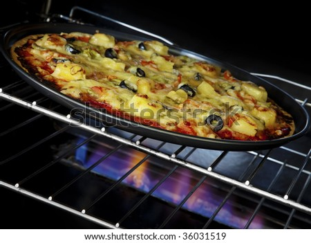 Delicious pizza cooking in a gas oven - stock photo