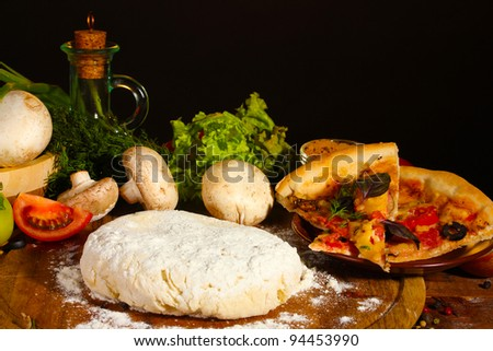 delicious pizza dough, spices and vegetables on wooden table on brown background