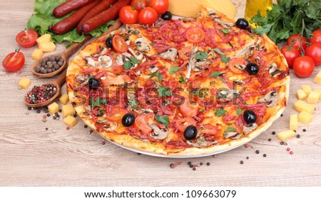 delicious pizza, vegetables and salami on wooden table