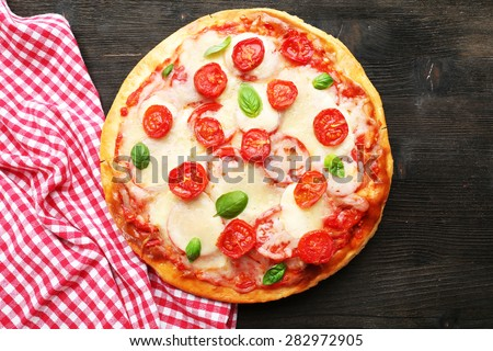 Delicious pizza with cheese and cherry tomatoes on wooden table, top view