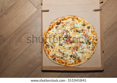 Delicious pizza with cheese, ham, eggplant with garlic, pepper, feta cheese, mushrooms and pizza sauce - stock photo