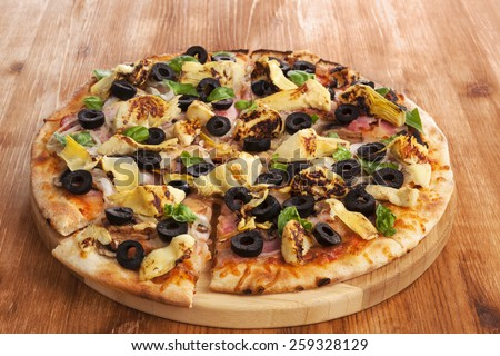 Delicious pizza with fresh herbs, olives on wooden background. Pizza eating.  - stock photo