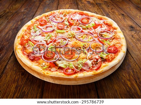 Delicious pizza with fresh onions, leek, bacon and cherry tomatoes - thin pastry crust isolated at wooden background on wooden desk - stock photo
