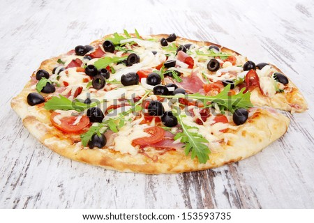 Delicious pizza with ham, black olives, fresh herbs and melted cheese on white wooden background. Traditional rustic style pizza eating. - stock photo