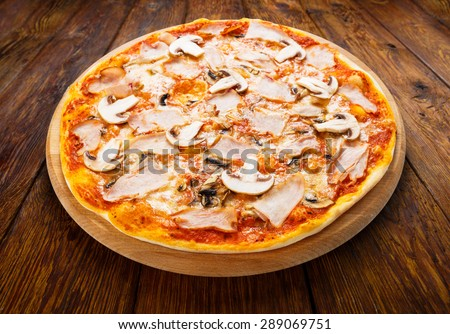 Delicious pizza with mushrooms and smoked chicken meat - thin pastry crust isolated at wooden background - stock photo