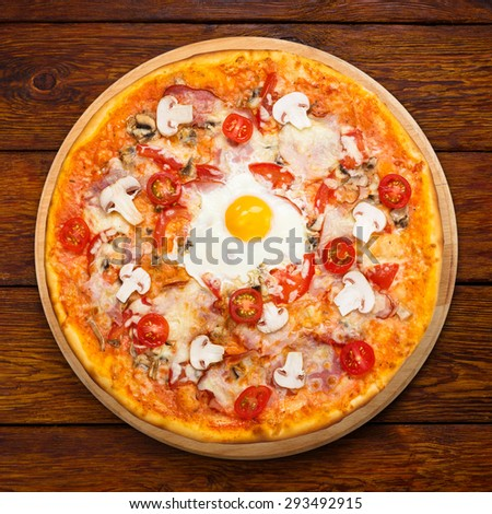 Delicious pizza with mushrooms, bacon, cherry tomatoes and egg - thin pastry crust at wooden background above view on wooden desk - stock photo