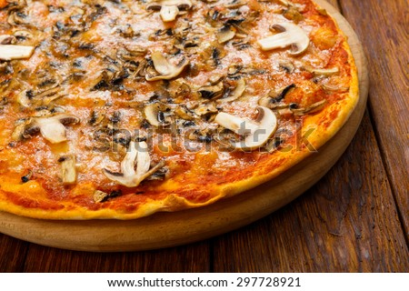 Delicious pizza with mushrooms - thin pastry crust isolated at wooden background on wooden desk - stock photo