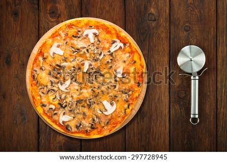 Delicious pizza with mushrooms - thin pastry crust isolated at wooden background with stainless steel cutter, above view - stock photo