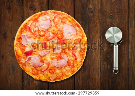 Delicious pizza with peppers, bacon and cherry tomatoes - thin pastry crust isolated at white background with stainless steel cutter, above view - stock photo