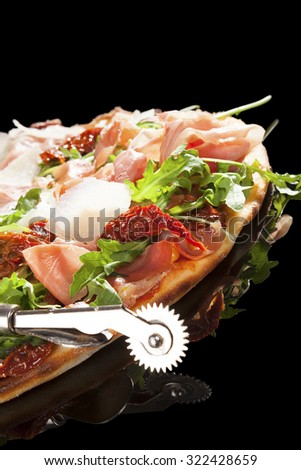 Delicious pizza with prosciutto ham, sundried tomatoes and fresh herbs. Culinary pizza eating.  - stock photo