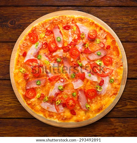 Delicious pizza with red and green hot chili peppers, bacon and cherry tomatoes - thin pastry crust at wooden background above view on wooden desk - stock photo