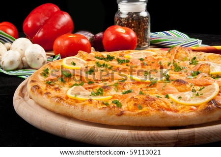 Delicious pizza with salmon and vegetables - stock photo