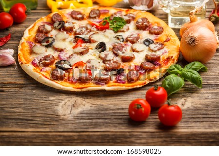 Delicious pizza with sausage, melted cheese and black olives - stock photo