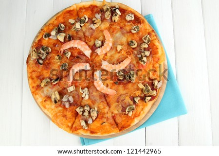 Delicious pizza with seafood on stand on wooden background