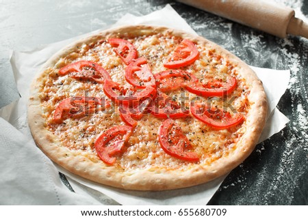 Delicious pizza with tomato on dark background
