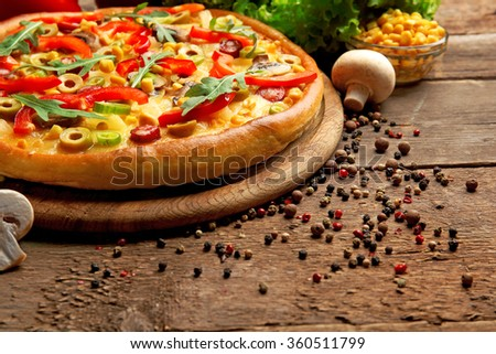 Delicious pizza with vegetables on wooden background - stock photo