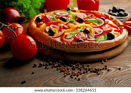 Delicious pizza with vegetables, on wooden table - stock photo