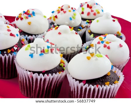 Delicious plate of cupcakes decorated with heart sprinkles on a red heart shaped plate over an isolated white background - stock photo