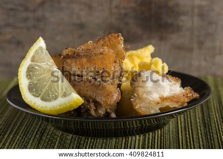 Delicious plate of fresh fried carp with polenta and one lemon slice - stock photo