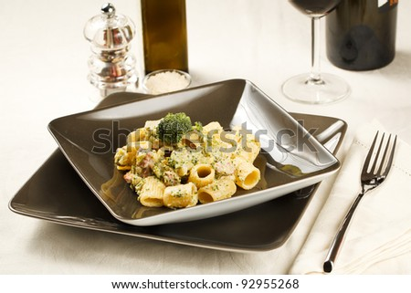 Delicious plate of macaroni pasta with broccoli and sausage in  a modern dishware and table setting - stock photo